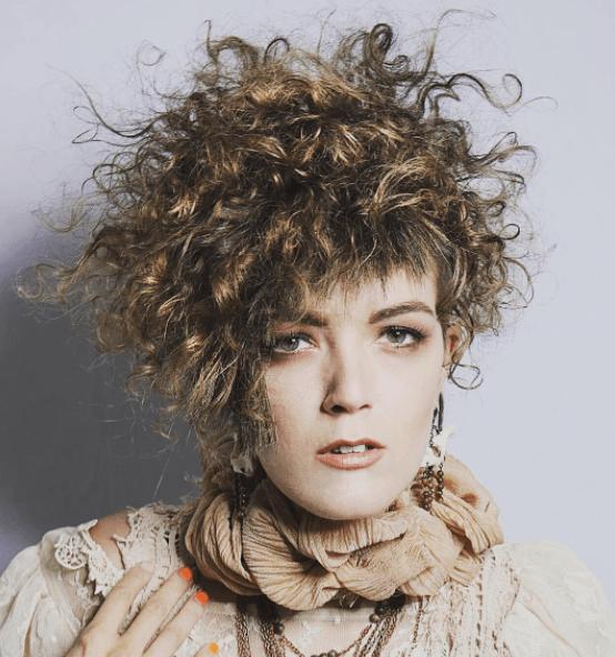 Coiffures des années 80 : image vue de face d'une femme aux cheveux châtain clair bouclés avec une micro frange