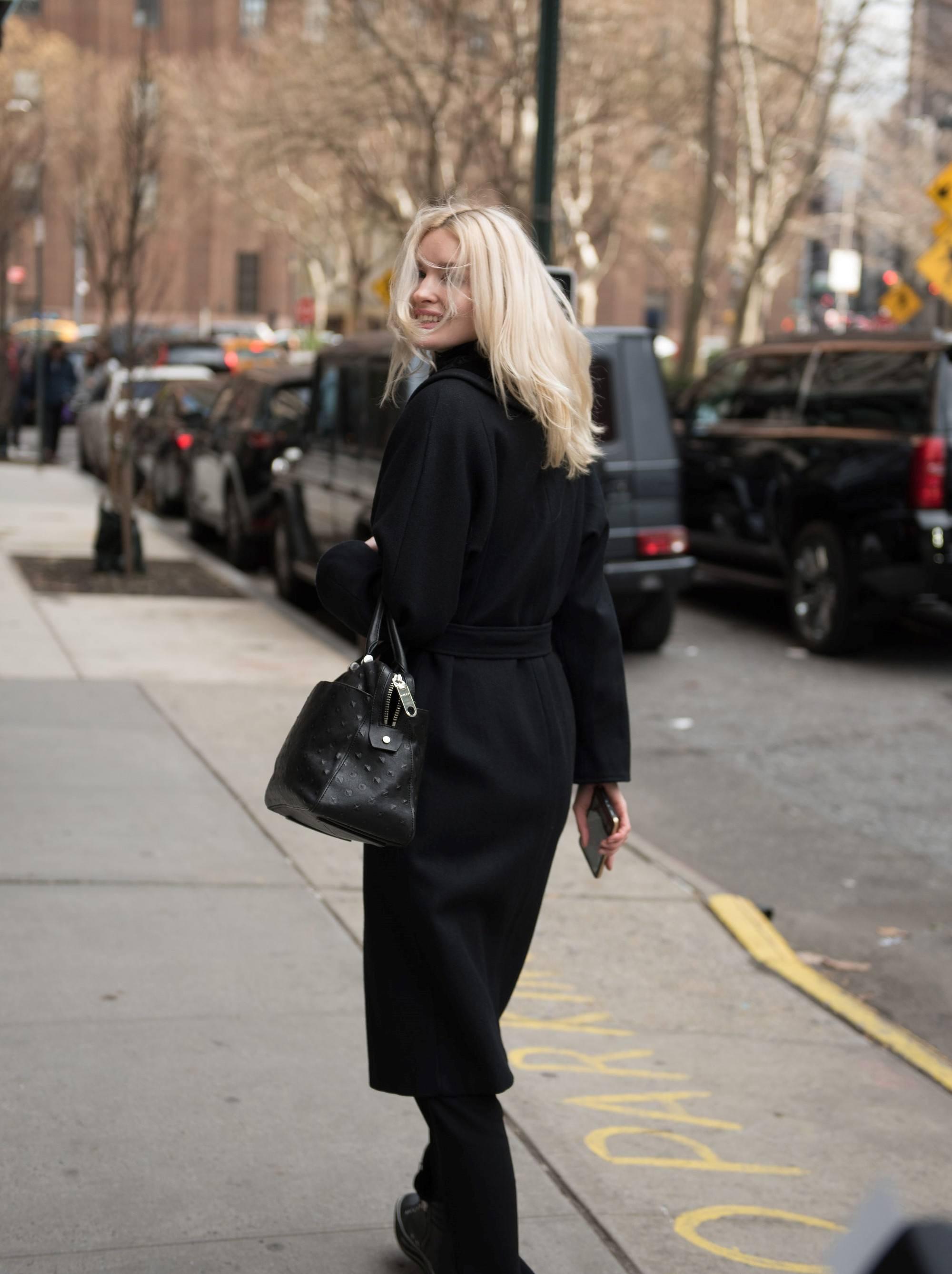 Femme avec de longs cheveux blonds décolorés balayés par le vent.