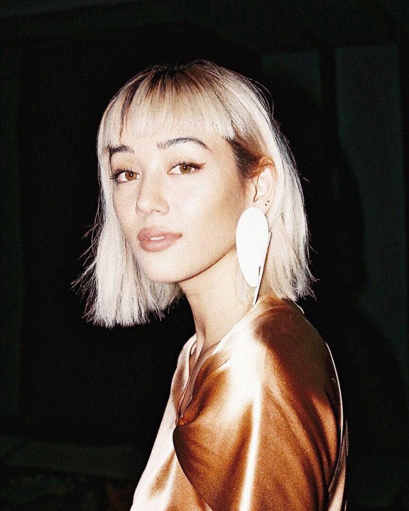 Guide des types de franges : Kim Jones avec un carré long blond décoloré coiffé d'une micro-frange, portant une boucle d'oreille en forme de coquillage avec un haut en satin orange.