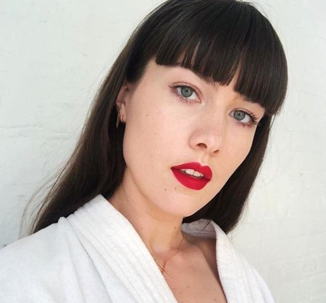 Guide du type de frange : Femme aux longs cheveux châtain foncé et à la frange émoussée, portant un haut blanc, avec du rouge à lèvres blanc et posant contre un mur blanc.