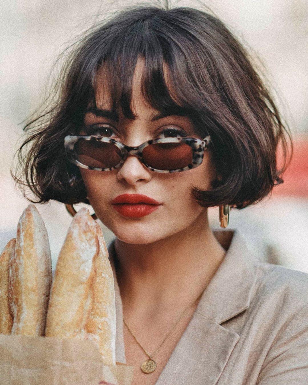 Femme avec une frange ondulée et une coupe de cheveux à la française.