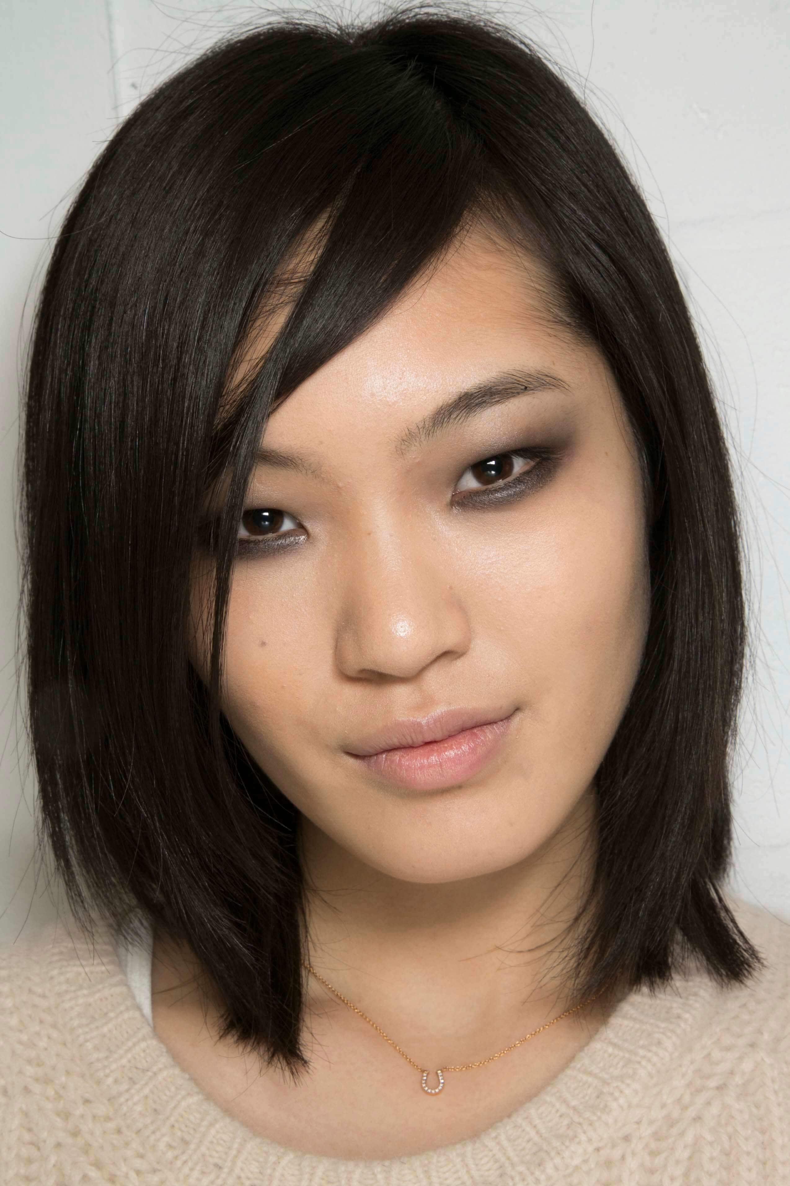 Gros plan d'une femme asiatique avec des cheveux noirs mi-longs et raides.