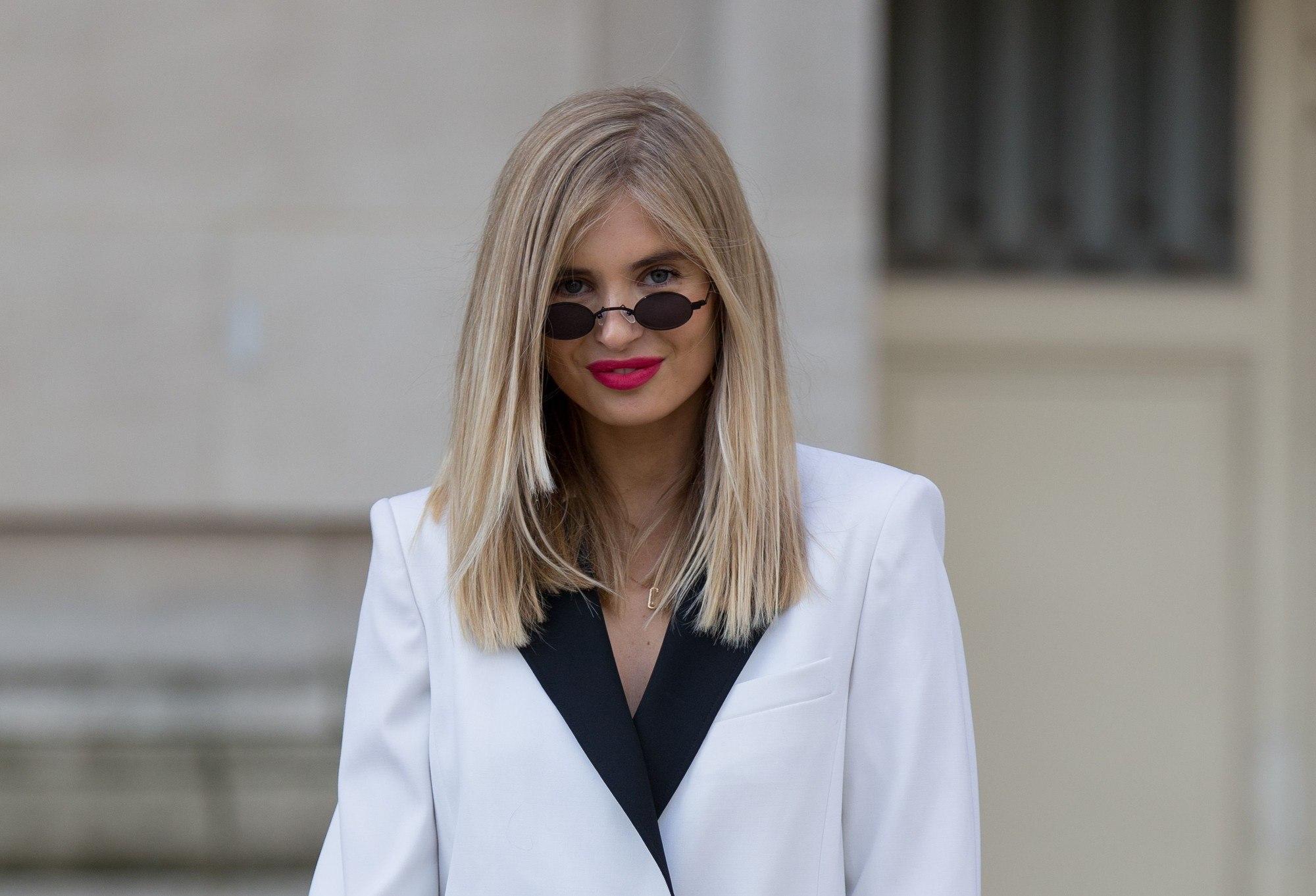 Plan rapproché d'un mannequin de style urbain aux racines blondes naturelles fondues dans une couleur de cheveux blonde cendrée, portant une veste de costume blanche et des lunettes de soleil, posant à l'extérieur.