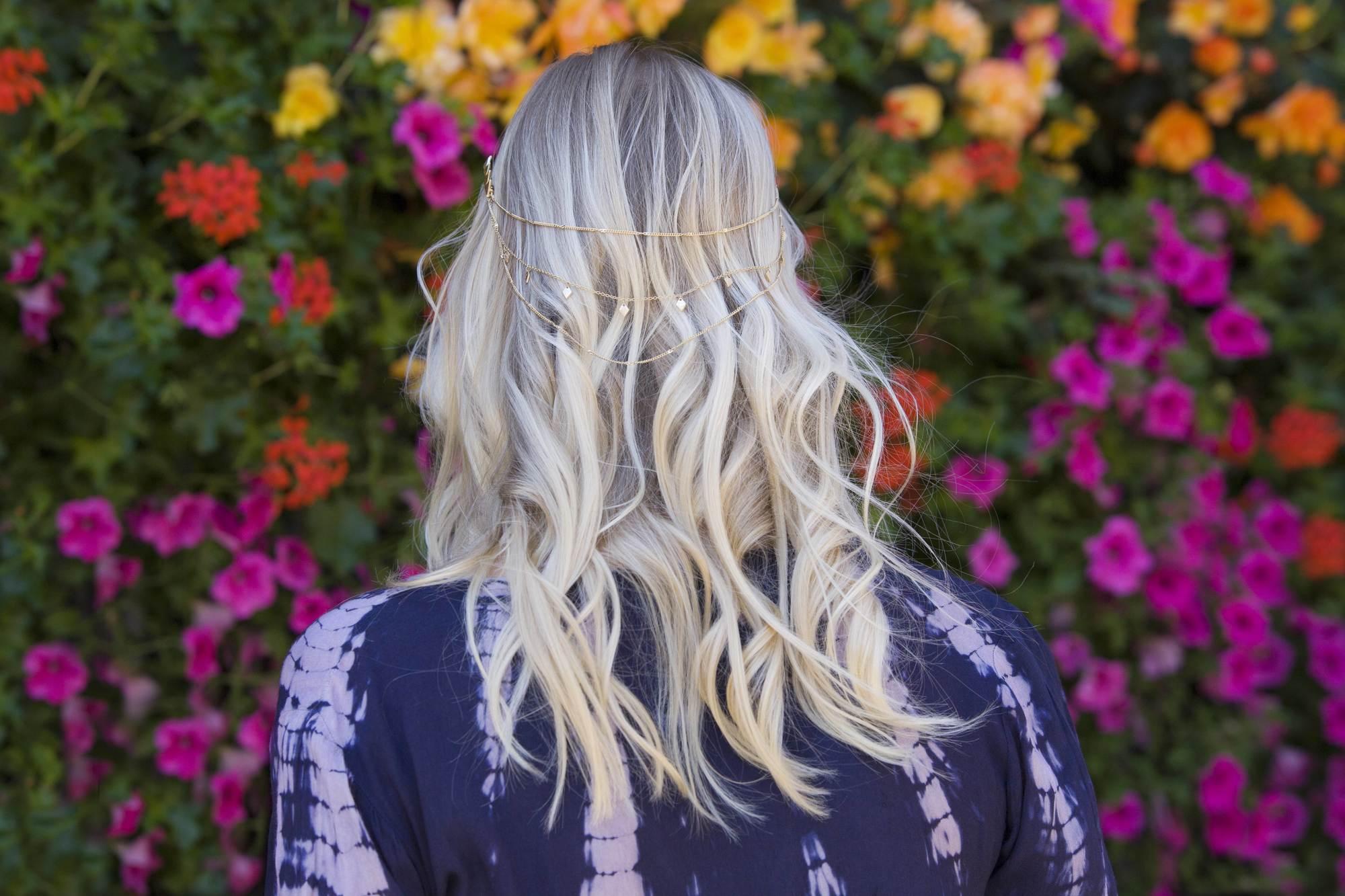 blond cendré : arrière de la tête d'une femme aux cheveux blonds ondulés et méchés, avec un accessoire pour cheveux de fête