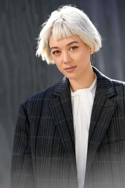 Femme avec un bob blond cendré brillant avec micro-frange, portant un blazer noir avec une chemise blanche.
