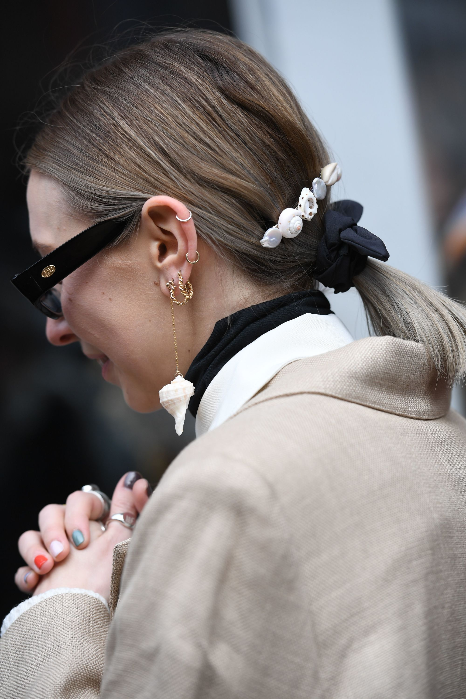 Plan de côté d'une femme aux cheveux courts, blond foncé à cendré, coiffés en queue de cheval et portant un manteau beige.