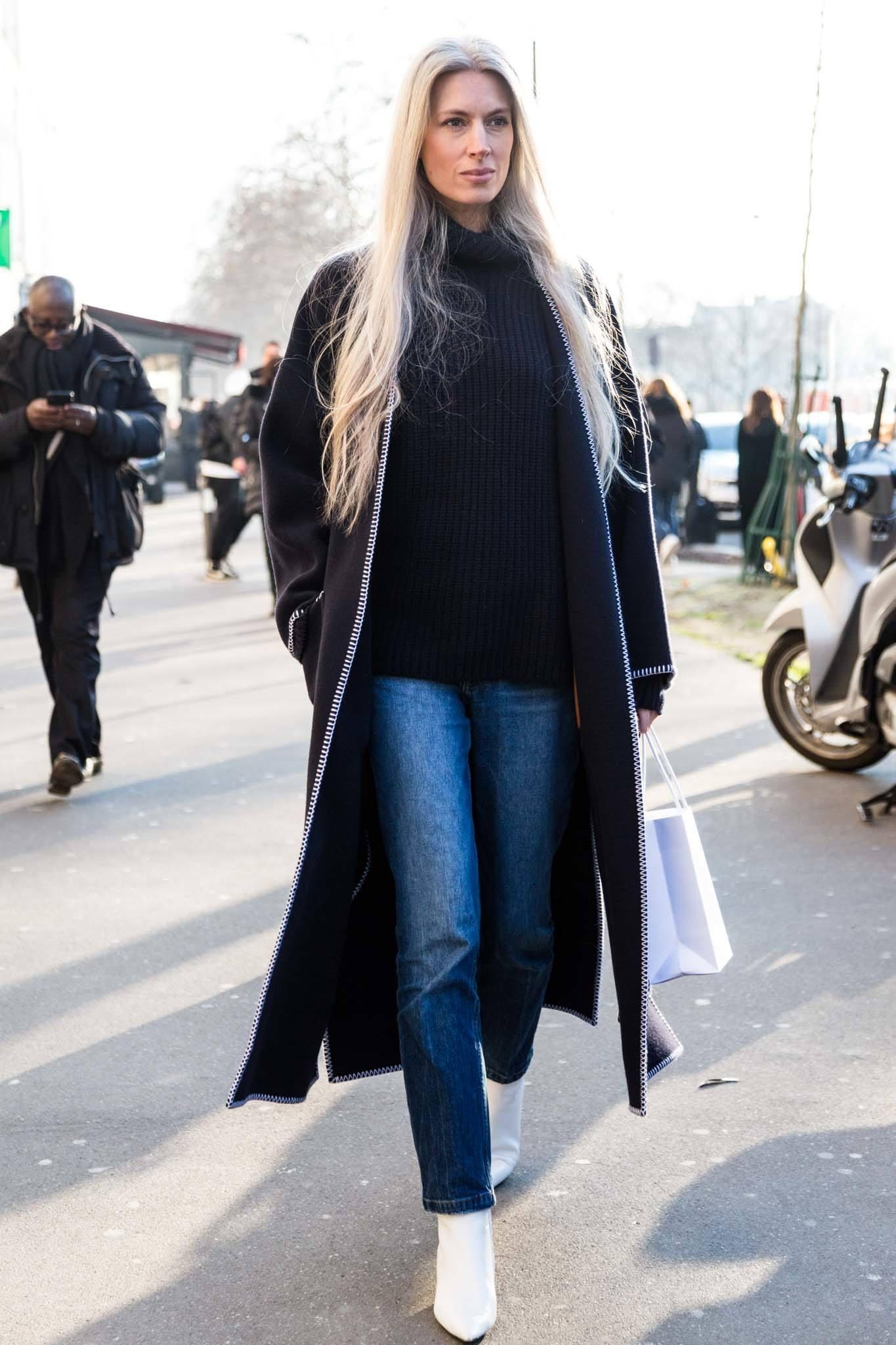 Cheveux blonds cendrés : Plan d'une femme dans la rue avec de longs cheveux blonds cendrés, portant un long manteau noir avec un jean et des baskets blanches à l'extérieur.