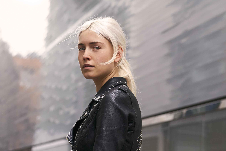 blonde cendrée : image d'une femme avec une queue de cheval basse blonde cendrée et perlée, portant du noir et posant dans la rue.