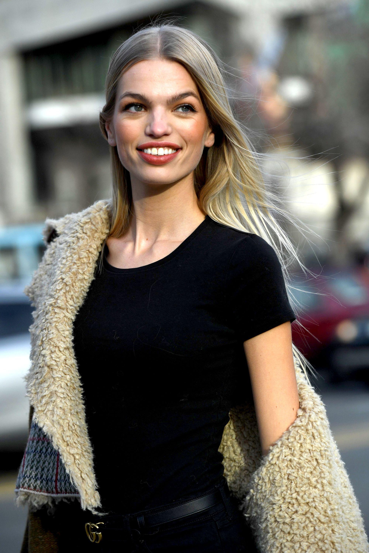 Photo d'une femme avec de longs cheveux blond cendré foncé avec des tons de miel, portant une chemise noire avec une veste borg à l'extérieur.