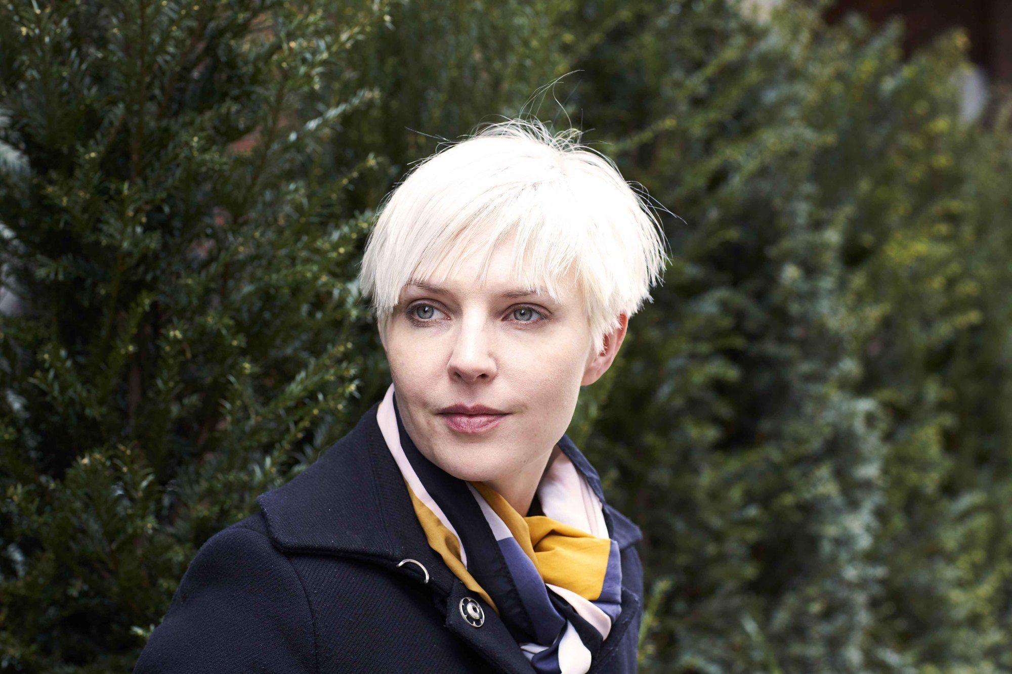 blonde cendrée : gros plan d'une femme aux cheveux courts, blonds nordiques, portant du noir et posant dans la rue.