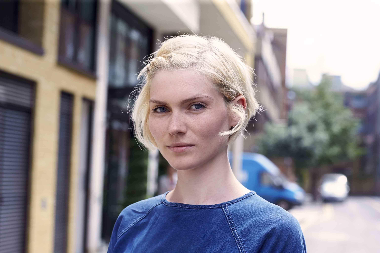 blonde cendrée : image de face d'une femme aux cheveux courts blond platine, portant du bleu et posant à l'extérieur