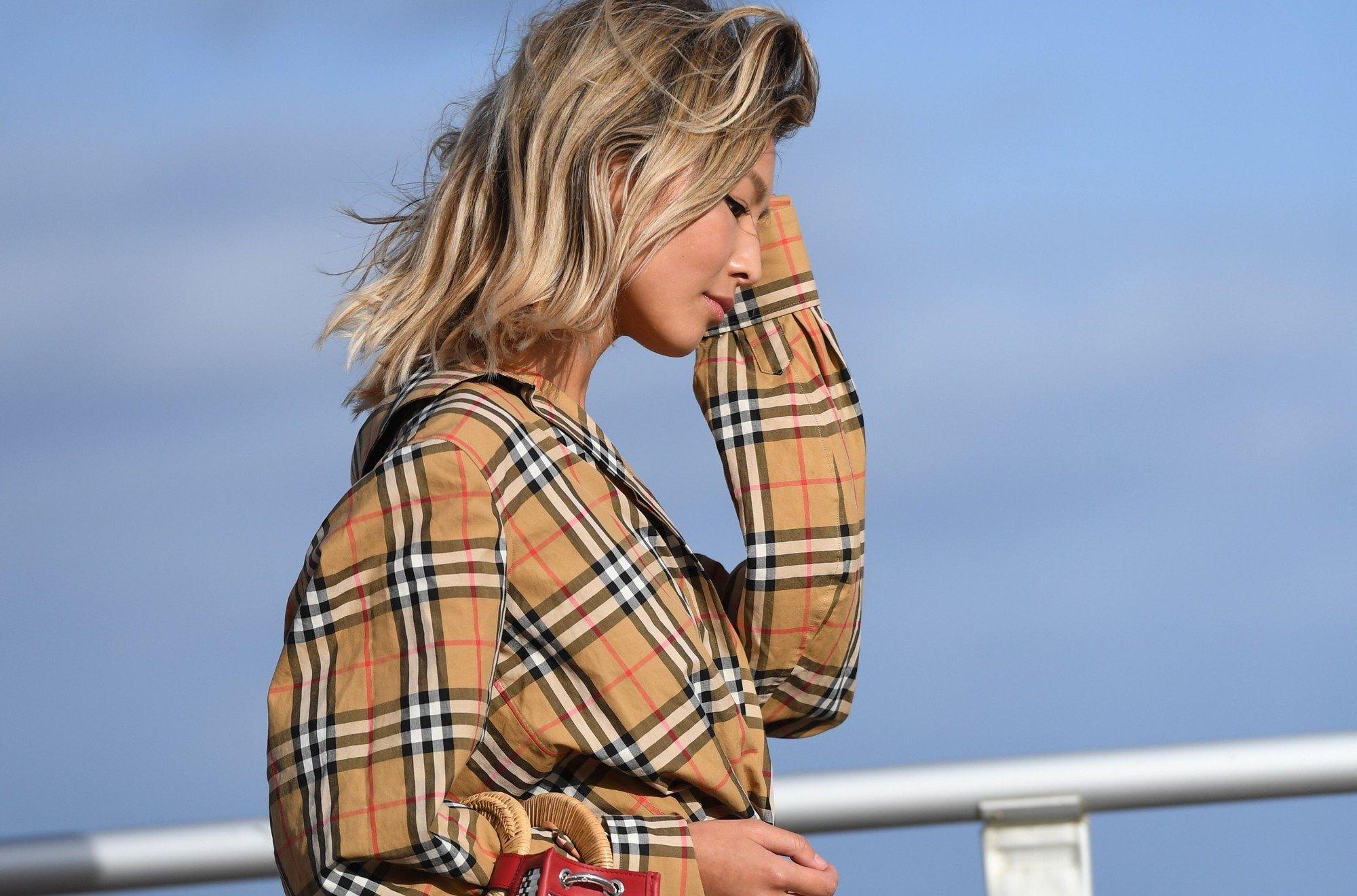 photo en gros plan d'un mannequin de style urbain aux cheveux blonds cendrés sableux, portant une veste à carreaux et posant dans la rue, tenant une pochette.