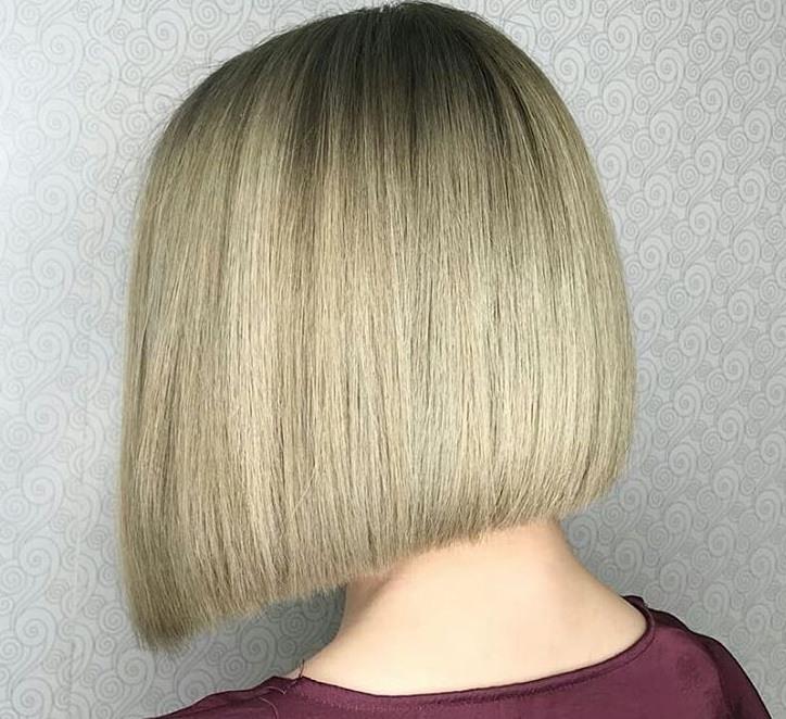 plan rapproché d'une femme avec une coupe de cheveux blonde cendrée, portant un haut rouge et posant dans un salon de coiffure