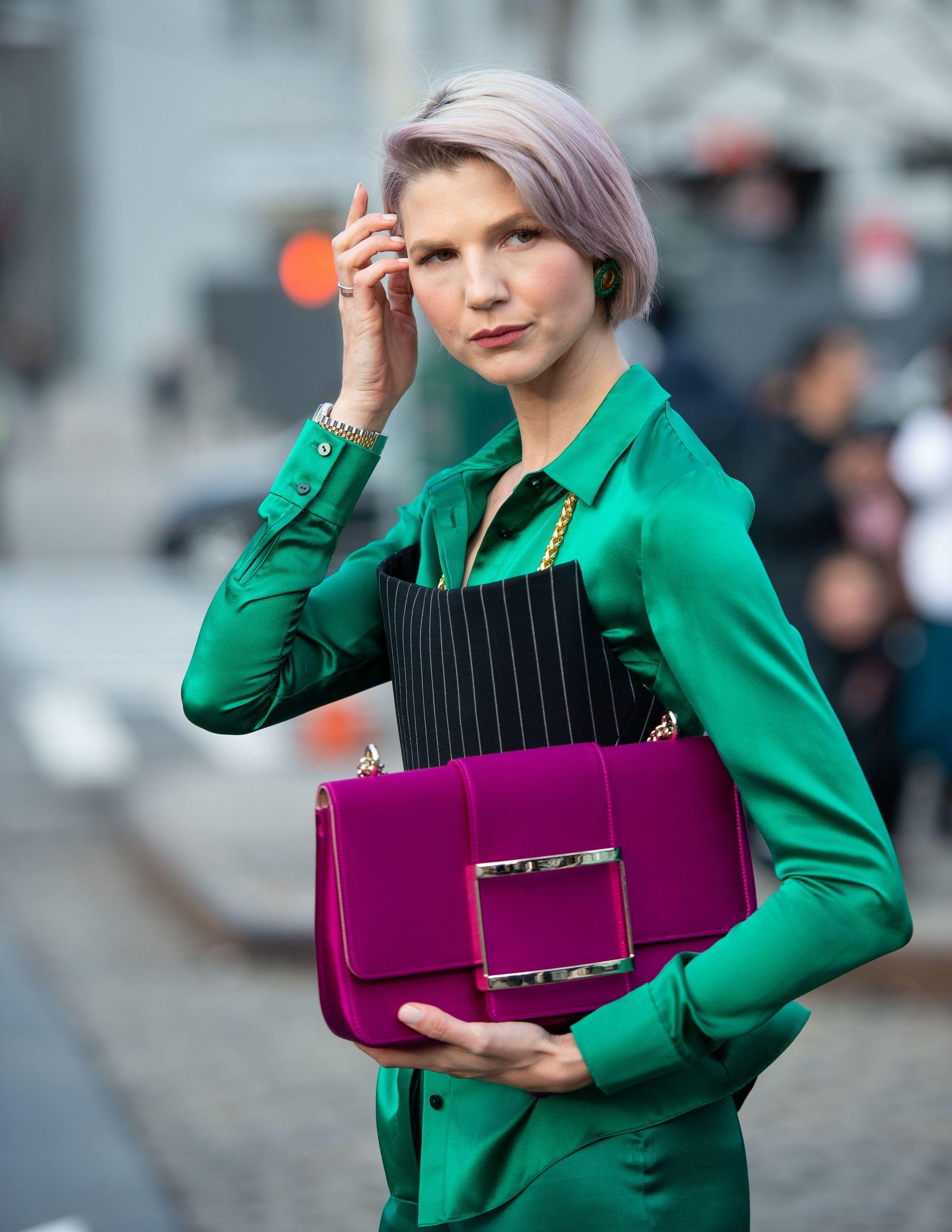 Femme avec un cheveu blond cendré avec un lavis lilas, portant un costume vert émeraude et tenant un sac violet à l'extérieur.
