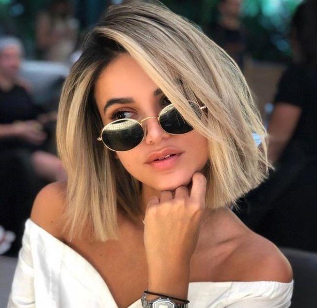 plan rapproché d'une femme avec une coiffure blonde cendrée balayée sur le côté, portant des lunettes de soleil noires et une chemise blanche, posant dans un salon de coiffure