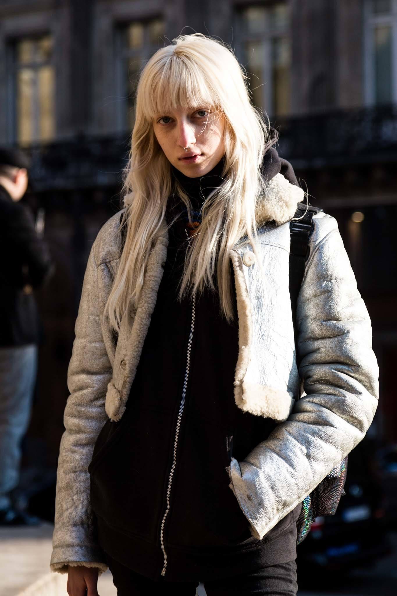 Prise de vue d'un mannequin de style urbain avec de longs cheveux blonds cendrés et une frange complète, portant des vêtements d'hiver et posant à l'extérieur.
