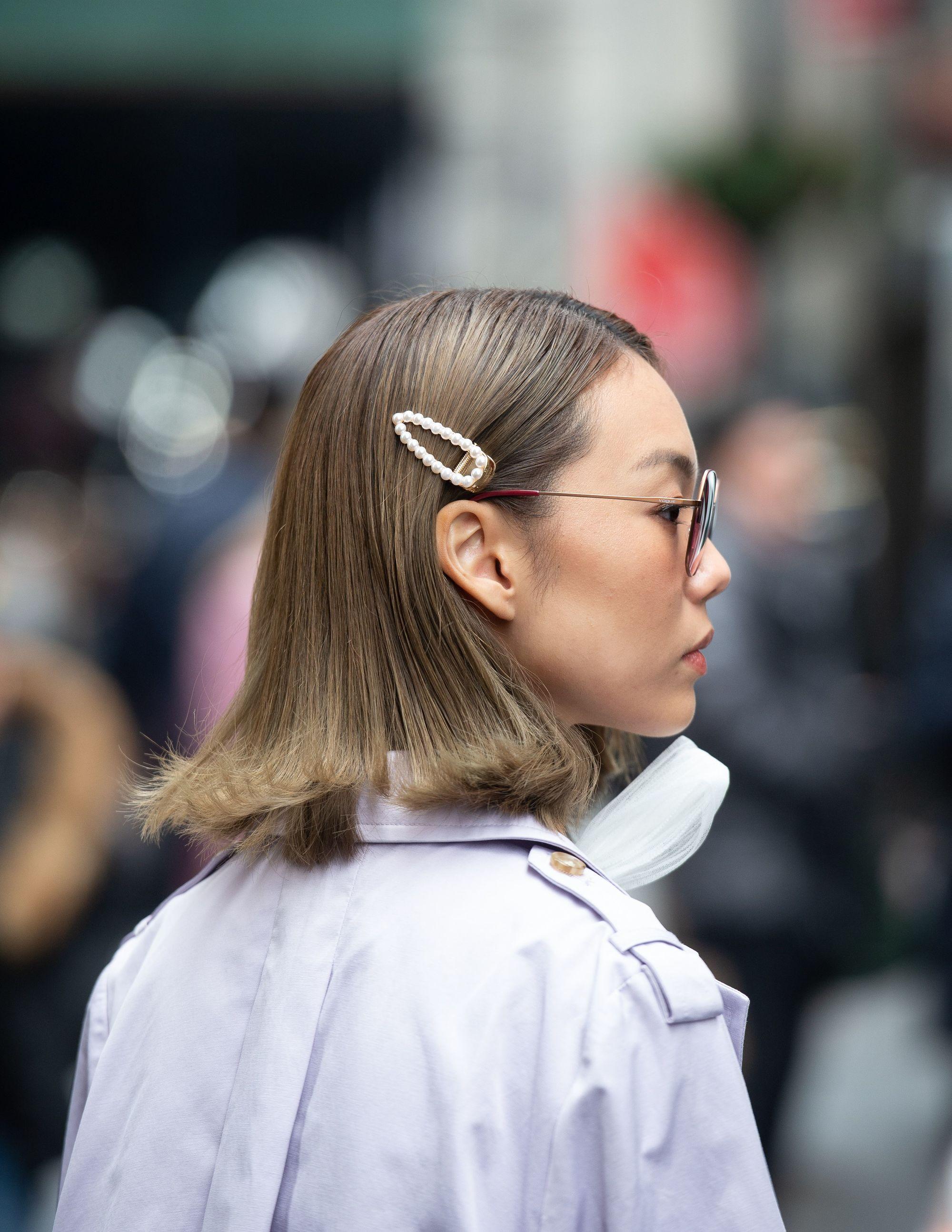 Cheveux blonds cendrés : Vue de côté d'une femme aux cheveux blonds cendrés moyens avec une barrette en forme de perle dans la rue.