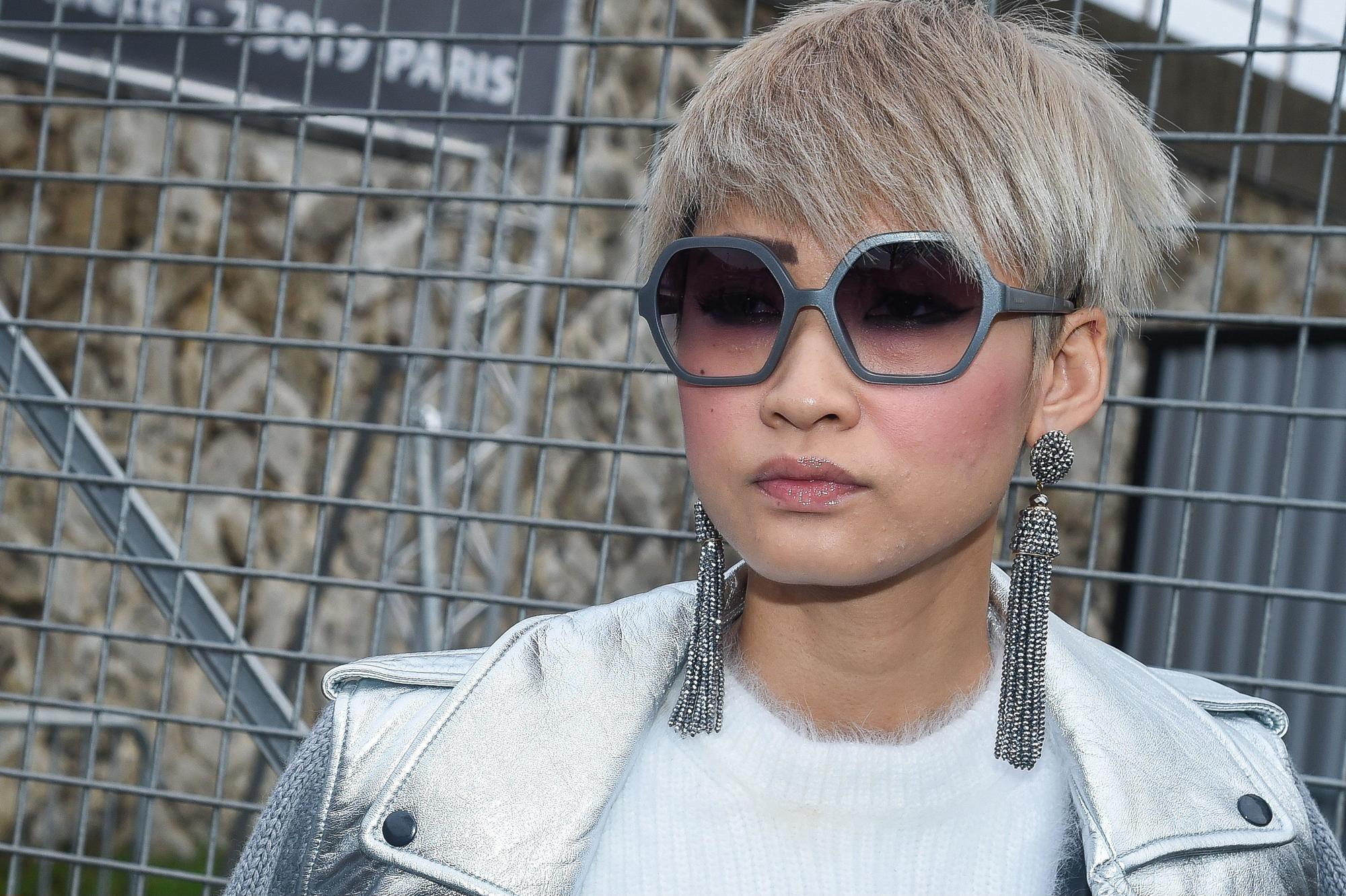 photo de style urbain d'une femme avec une coupe de cheveux pixie blonde cendrée argentée, portant des boucles d'oreilles et de grosses lunettes de soleil, avec un haut et une veste blancs, posant dans la rue.