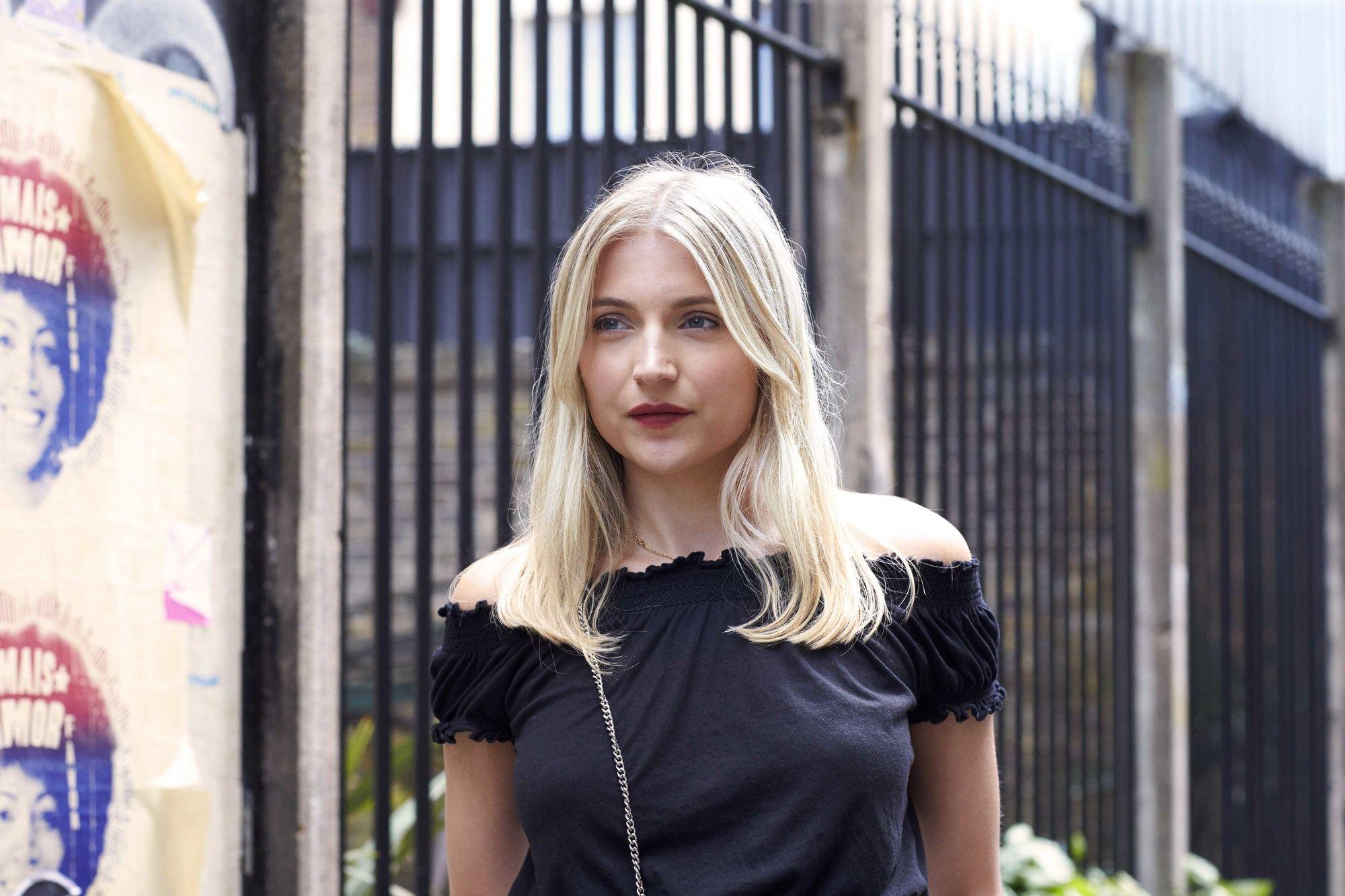 blonde cendrée : plan rapproché d'une femme aux cheveux blond clair moyen, portant un haut noir et posant dans la rue