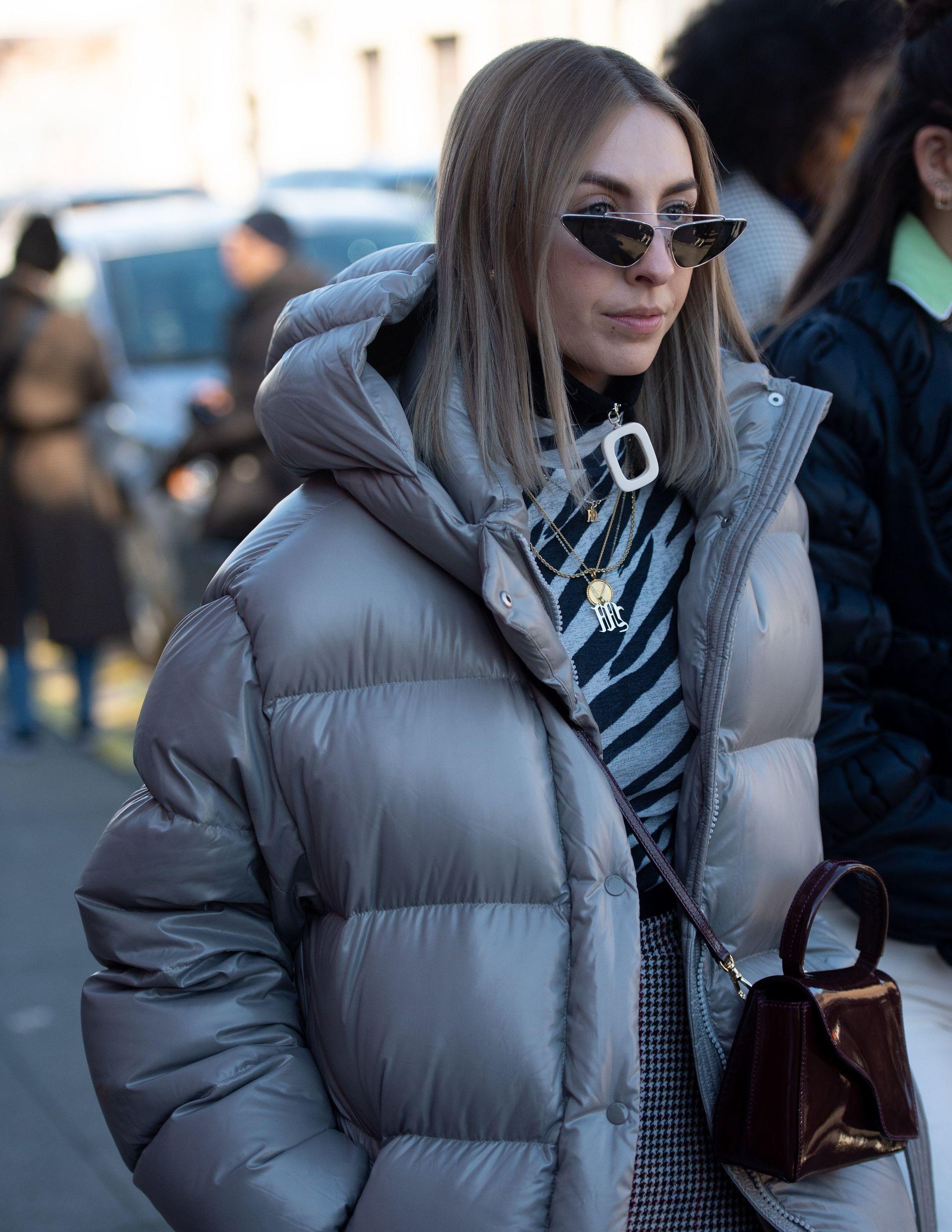 Femme aux cheveux châtain foncé longueur épaule avec une ombre blonde cendrée, portant une veste polaire grise avec des micro lunettes à l'extérieur.
