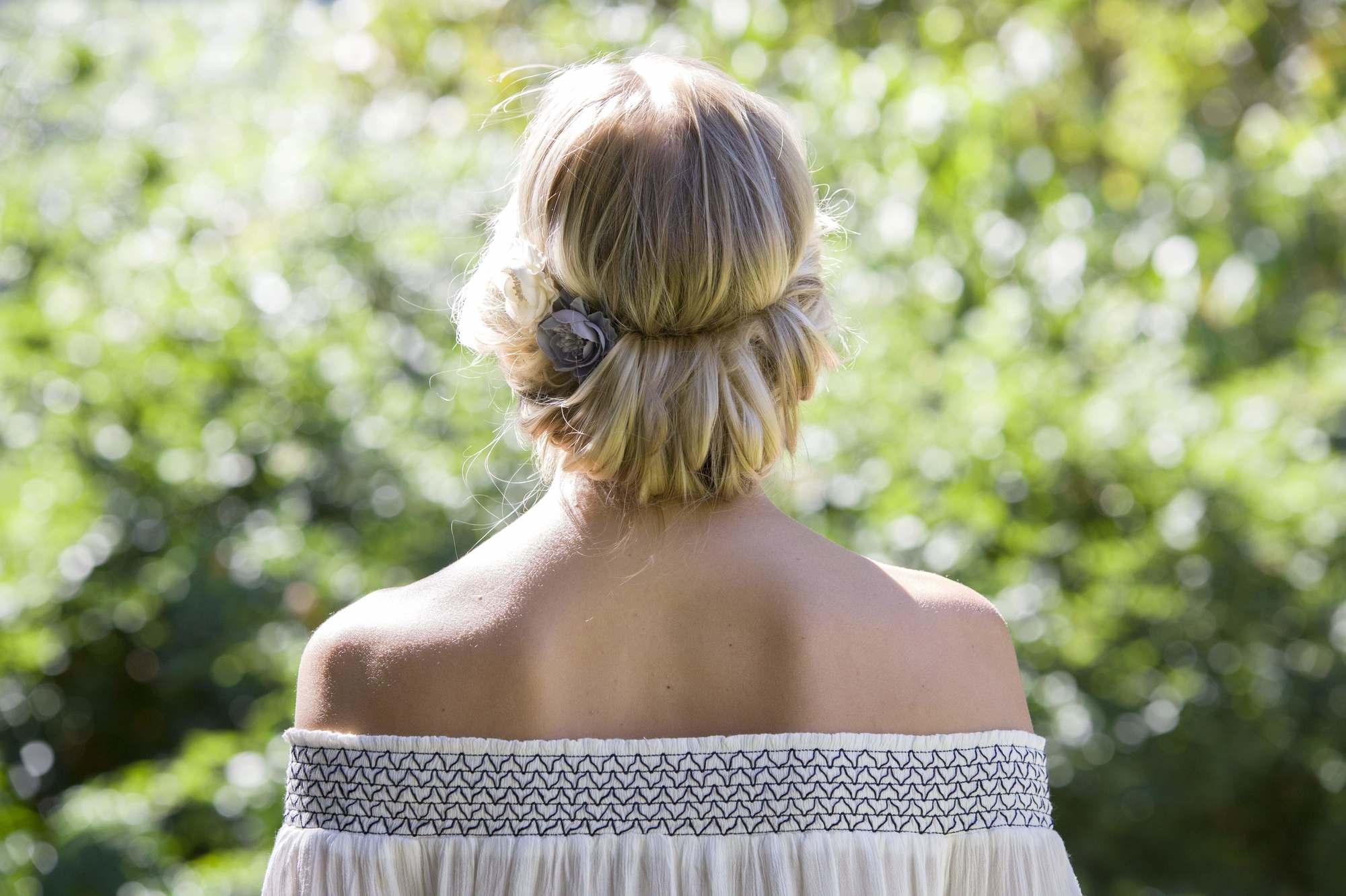 blonde cendrée : arrière de la tête d'une femme aux cheveux blonds tordus en une coiffure de type tuck, portant un haut bardot décolleté et posant à l'extérieur.