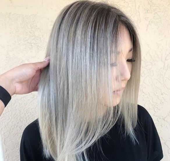plan rapproché d'une femme aux cheveux moyens, blond cendré glacé, portant un haut noir
