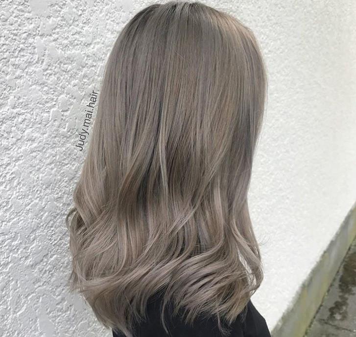 plan rapproché d'une femme aux cheveux blonds cendrés métalliques, portant un haut noir et posant à l'extérieur