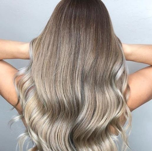 blonde cendrée : plan arrière d'une femme aux longs cheveux cendrés fumés, bouclés aux extrémités, posant dans un studio.