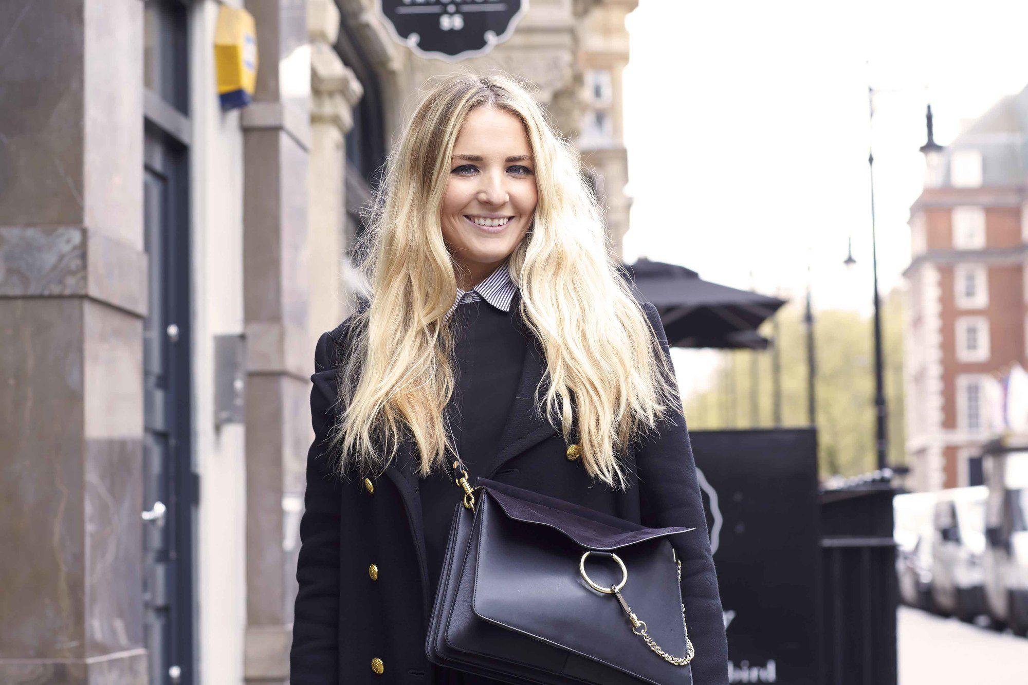 blonde cendrée : plan rapproché d'une femme aux longs cheveux blonds ondulés, portant tout le noir et posant dans la rue