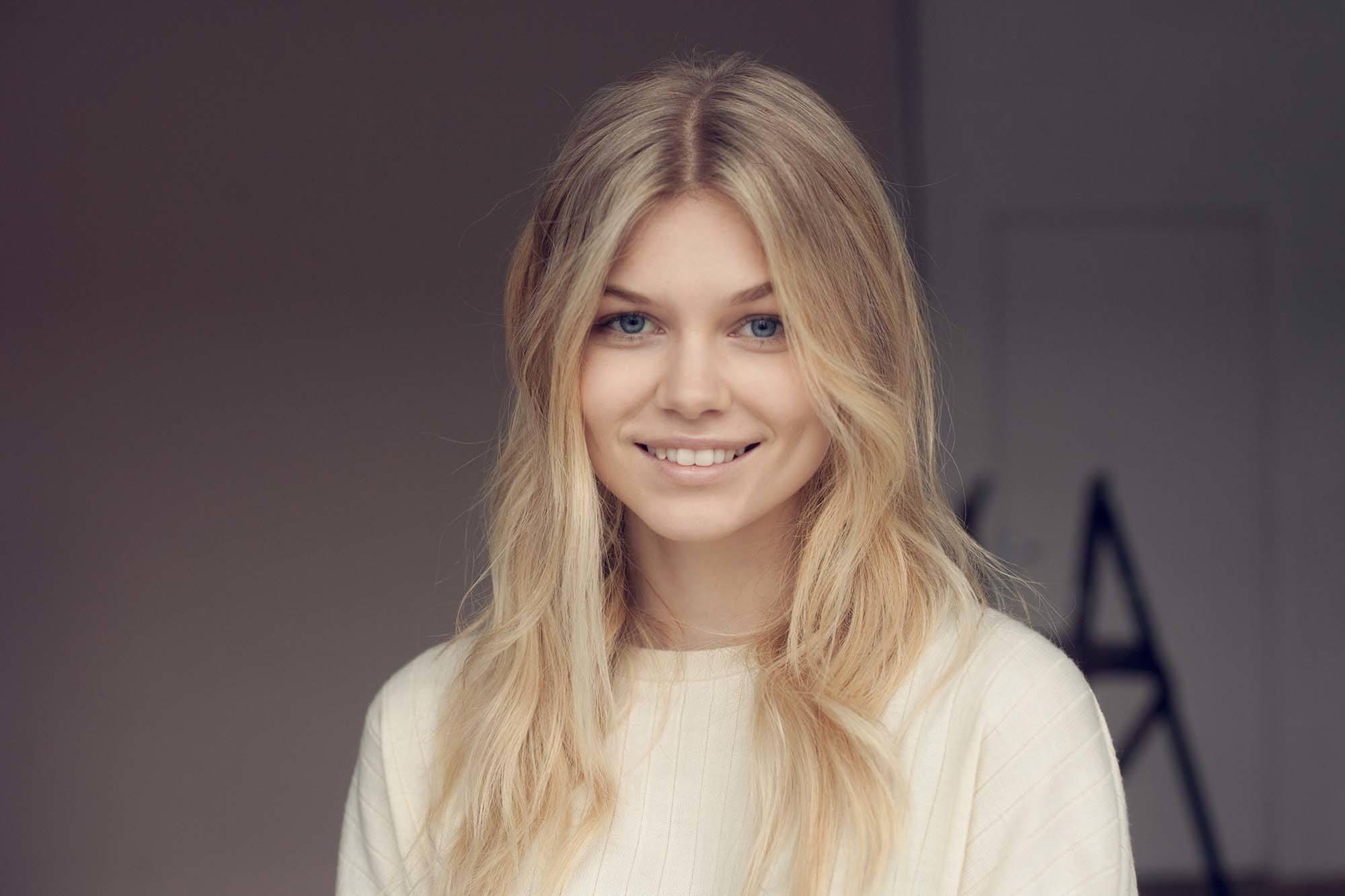 cheveux blond cendré : plan rapproché d'une femme aux cheveux blond cendré moyen et clair, coiffés en ondulations, portant un haut blanc et souriant.