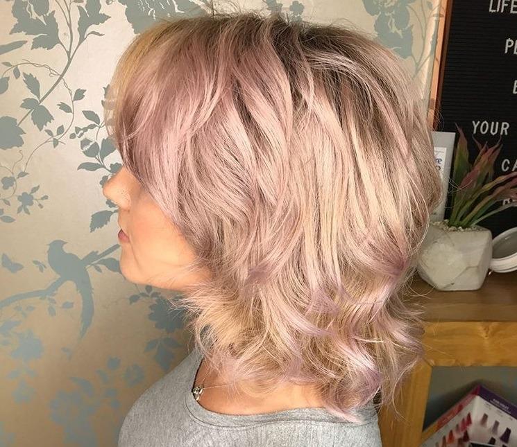plan rapproché d'une femme aux cheveux hirsutes blonds cendrés roses, portant un haut gris et posant sur un fond argenté dans une chambre à coucher