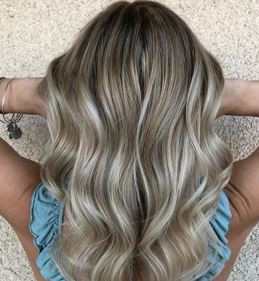 plan rapproché de dos d'une femme avec des lumières de babylight blond cendré dans ses cheveux blond foncé, portant un haut bleu et posant sur un fond blanc.