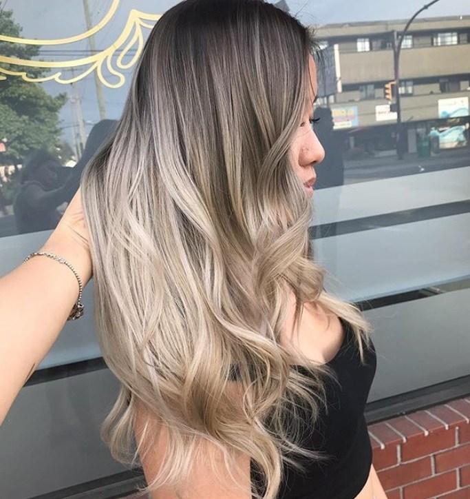 plan rapproché d'une femme aux racines foncées et aux longs cheveux blonds cendrés, vêtue de noir et posant devant un salon de coiffure