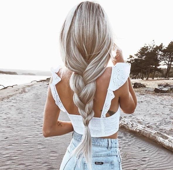 photo de dos d'une femme aux cheveux blonds cendrés argentés tressés, portant un haut blanc et un jean, posant sur une plage.