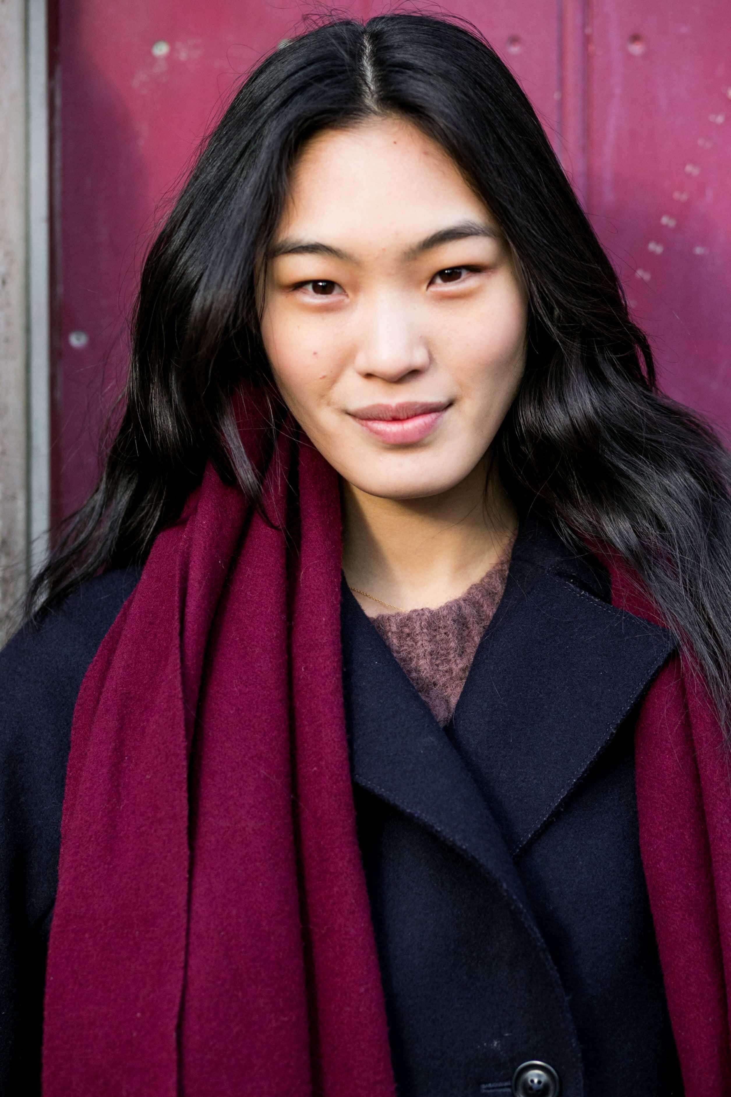 Coiffures asiatiques : Femme asiatique aux cheveux bruns foncés ondulés portant un manteau d'hiver et une écharpe.