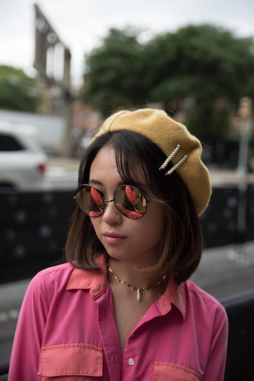 Femme aux cheveux asiatiques courts avec une frange latérale, un béret et des pinces à cheveux.