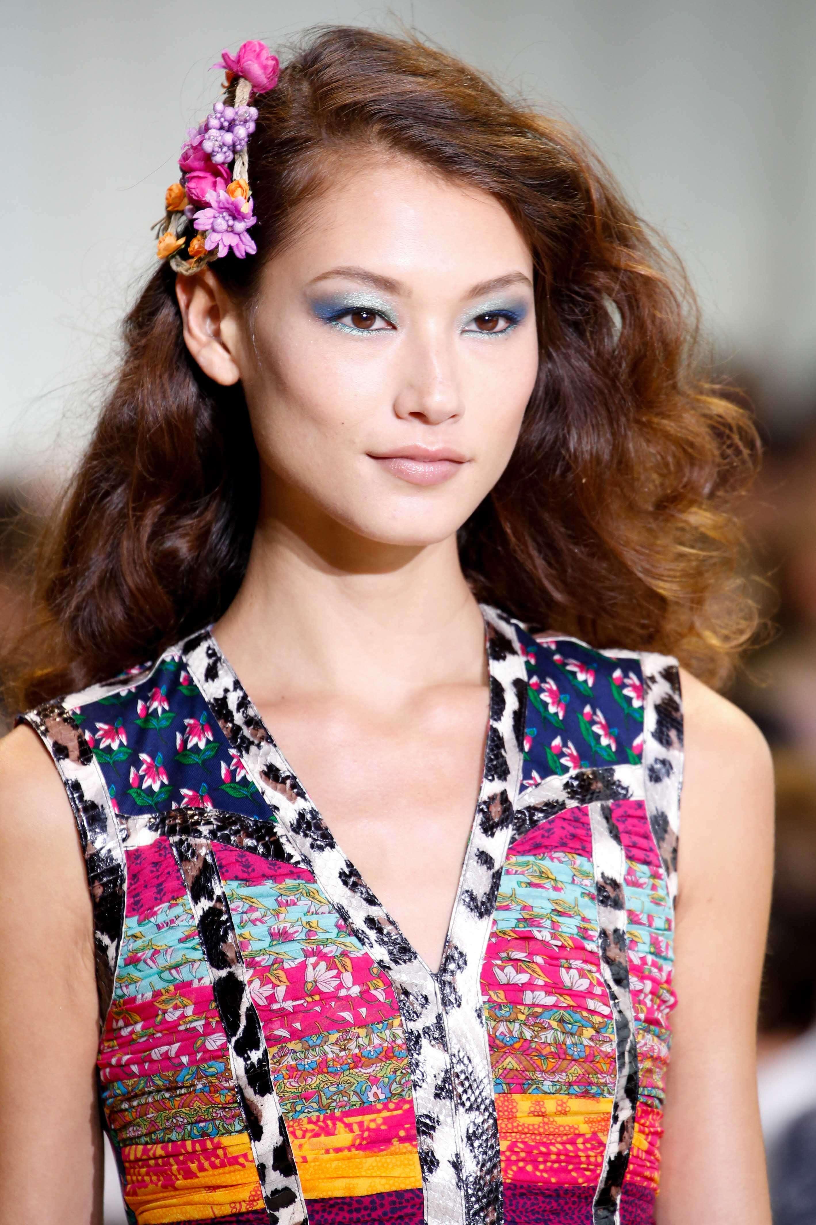 Coiffures asiatiques : Femme asiatique aux cheveux bouclés bruns caramels dorés avec un accessoire de cheveux floral portant une robe à motifs.