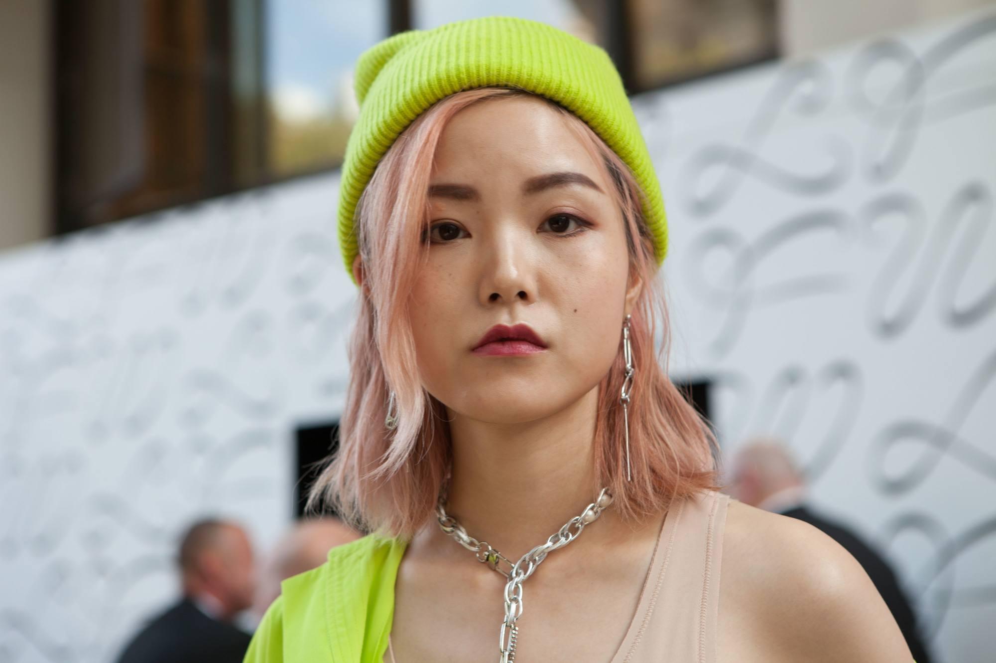 Femme aux cheveux asiatiques roses, longs d'épaule, avec un bonnet jaune fluo.
