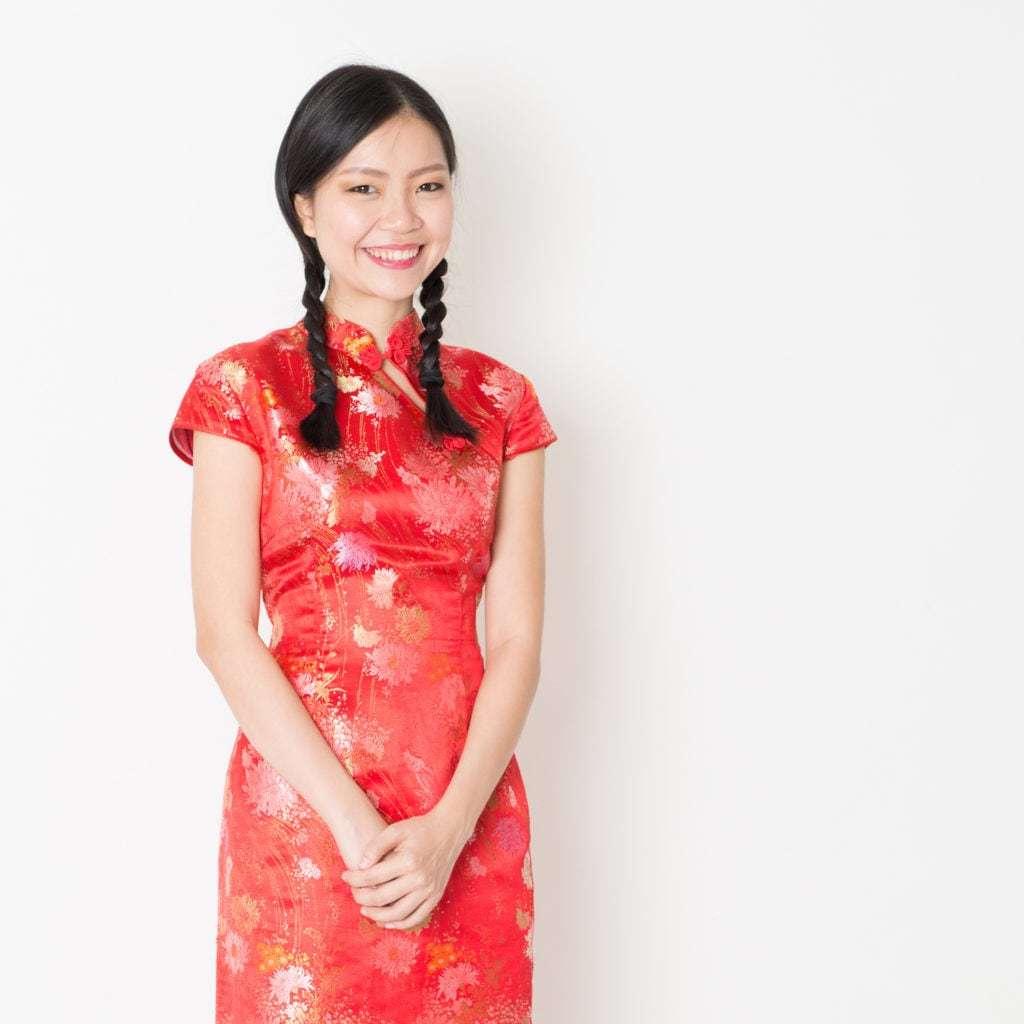 Coiffures asiatiques : Modèle asiatique aux cheveux bruns lisses avec des nattes tressées, portant une tenue traditionnelle rouge à fleurs.