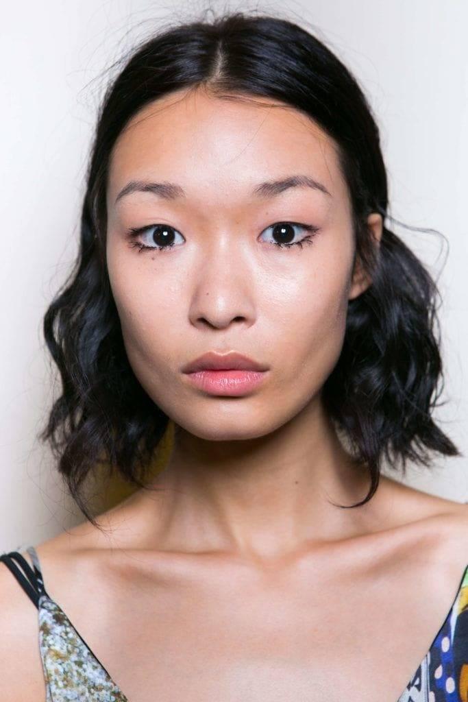 Coiffures asiatiques : Femme asiatique avec un carré long ondulé brun foncé.