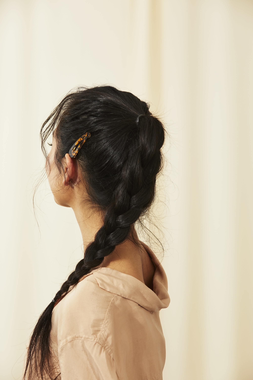 Femme aux longs cheveux asiatiques tressés coiffés en queue de cheval tressée avec une pince à cheveux.