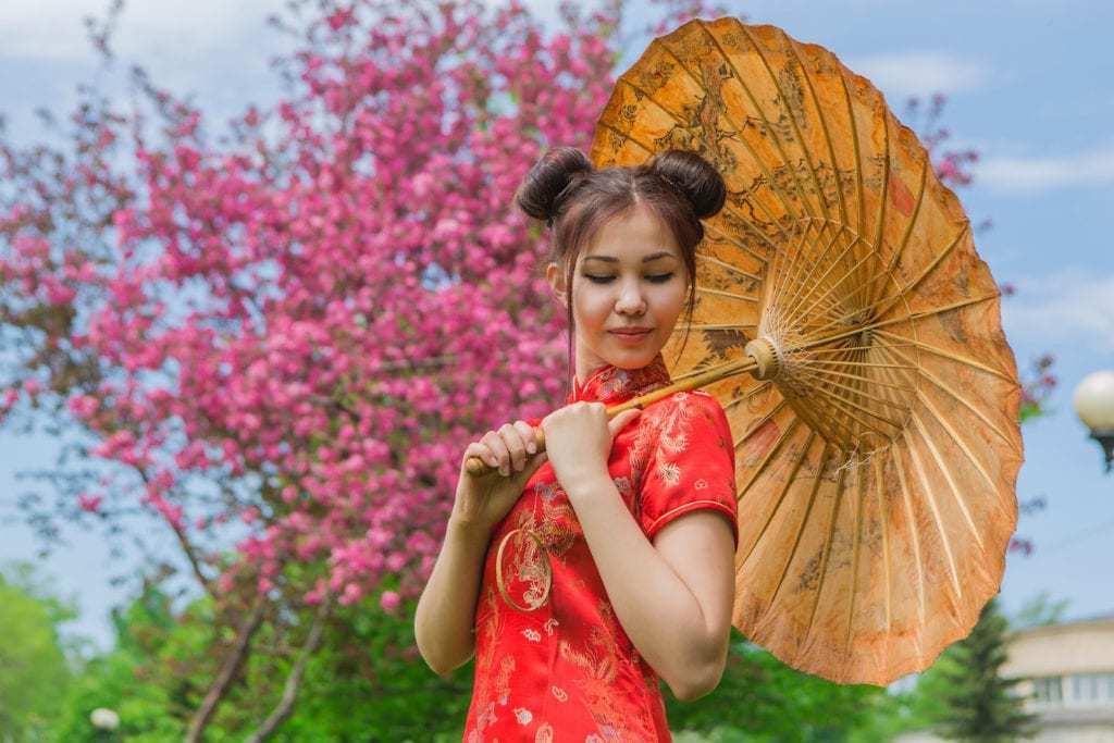 Coiffures asiatiques : Femme asiatique aux cheveux bruns et raides, coiffés en chignon spatial, portant une tenue traditionnelle rouge.