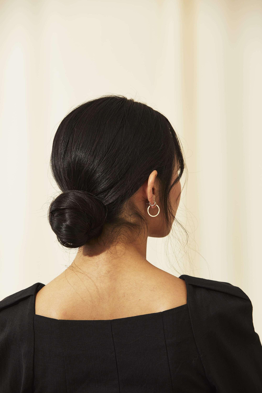 Femme aux cheveux asiatiques foncés coiffés en un chignon bas noué.