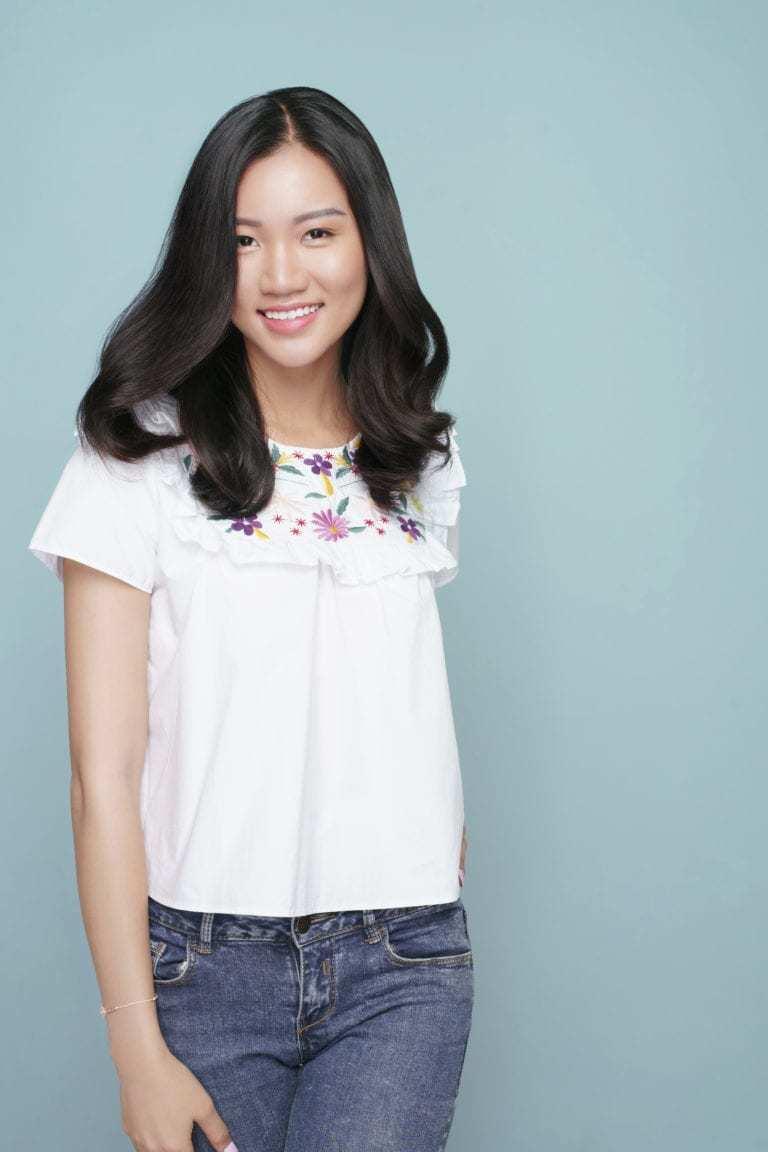 Coiffures asiatiques : Femme asiatique avec de longs cheveux bruns ondulés et bouclés, portant un haut blanc et un jean.