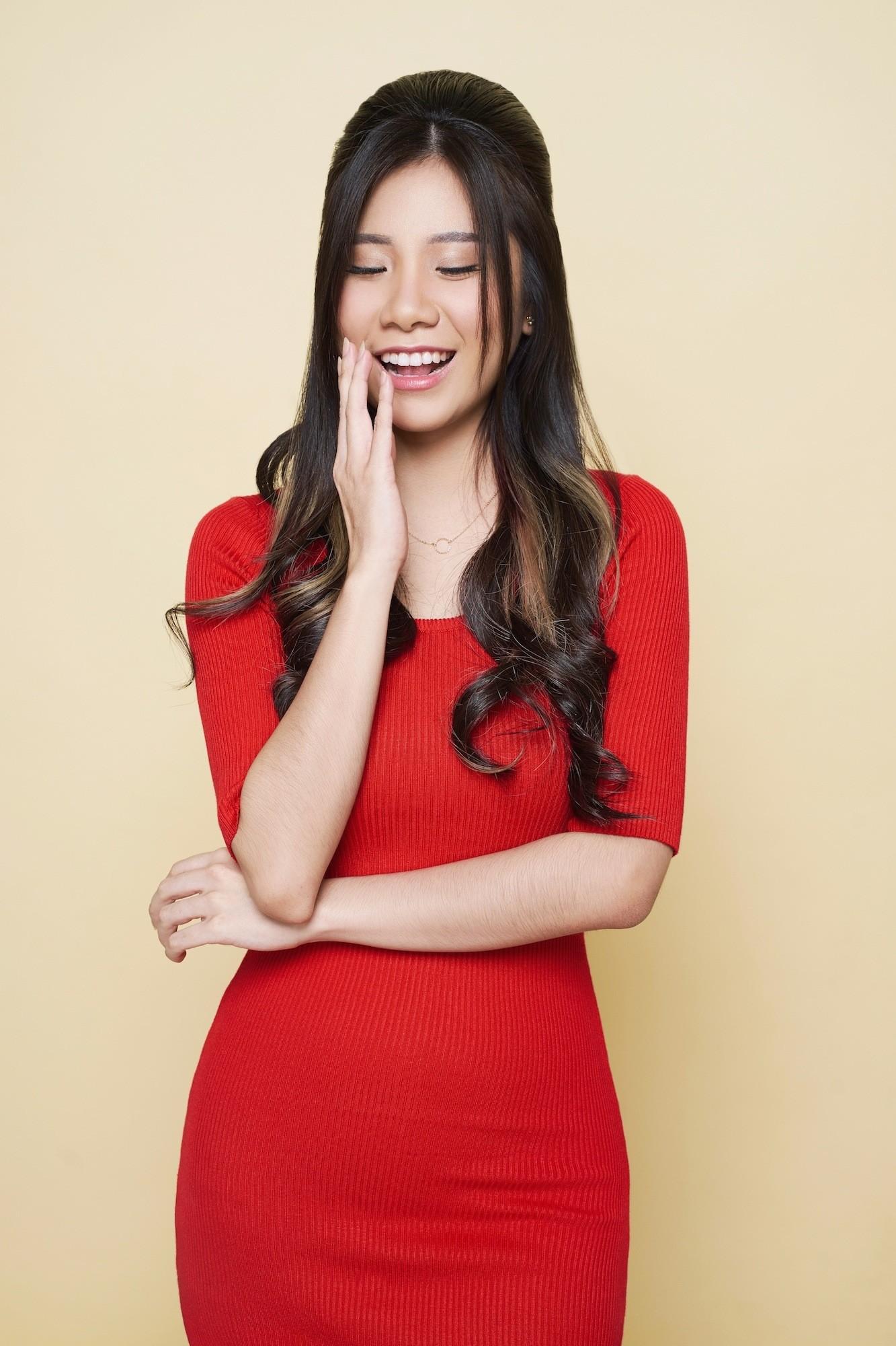 Coiffures asiatiques : Femme asiatique aux longs cheveux bruns ondulés en ruche portant une robe rouge.