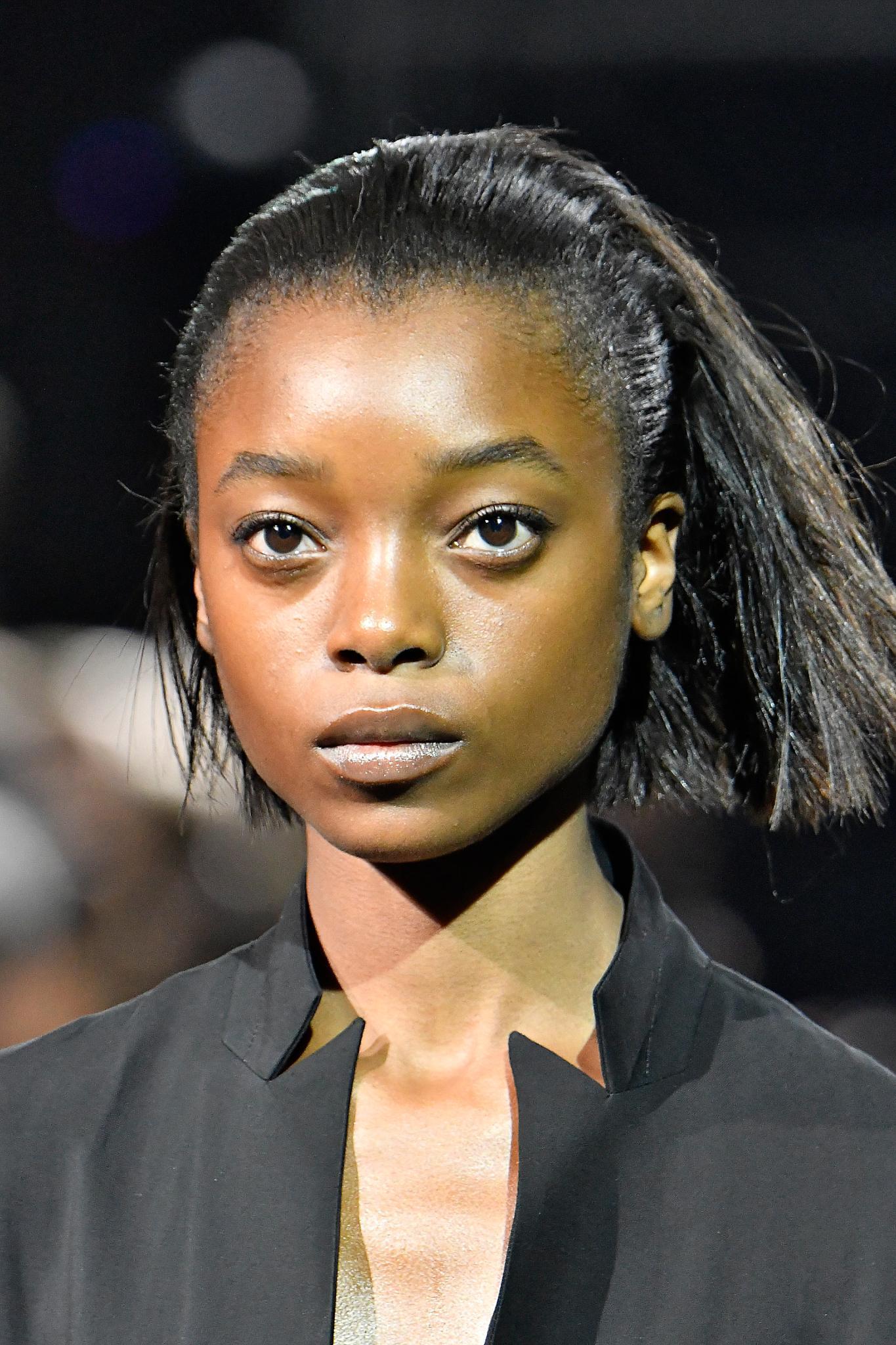 Idées de cheveux noirs courts : Mannequin noir avec un bob lissé/brossé en arrière.