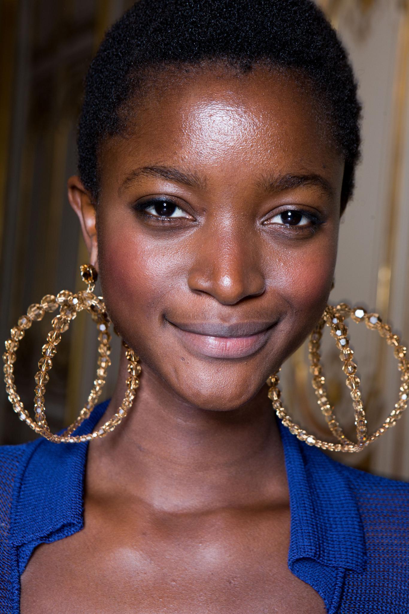 Cheveux noirs courts : Un modèle avec une coupe afro courte portant de grandes boucles d'oreilles dorées.