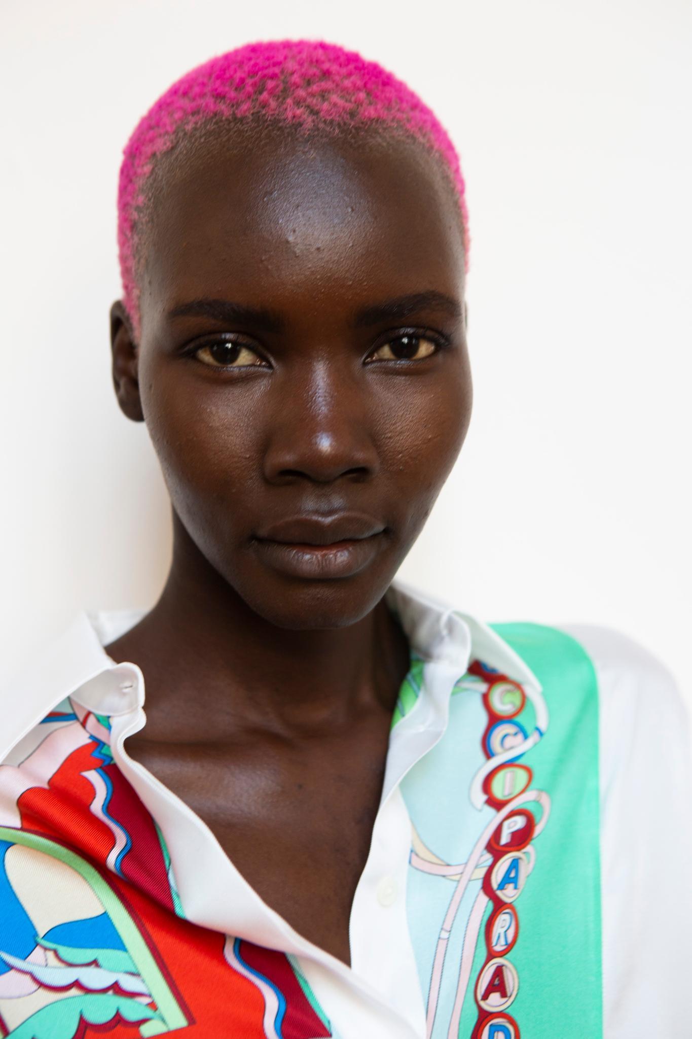 Cheveux noirs courts : Un mannequin noir avec une afro rose rasée.