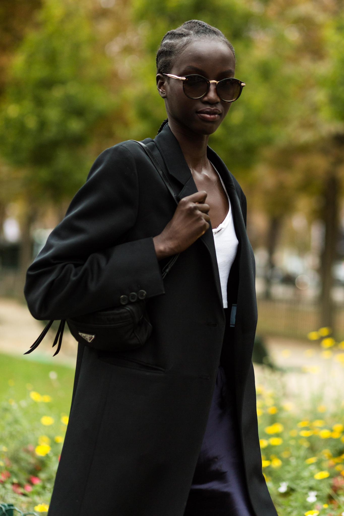 Idées de cheveux noirs courts : Un mannequin noir avec une coiffure en tresses à l'extérieur.