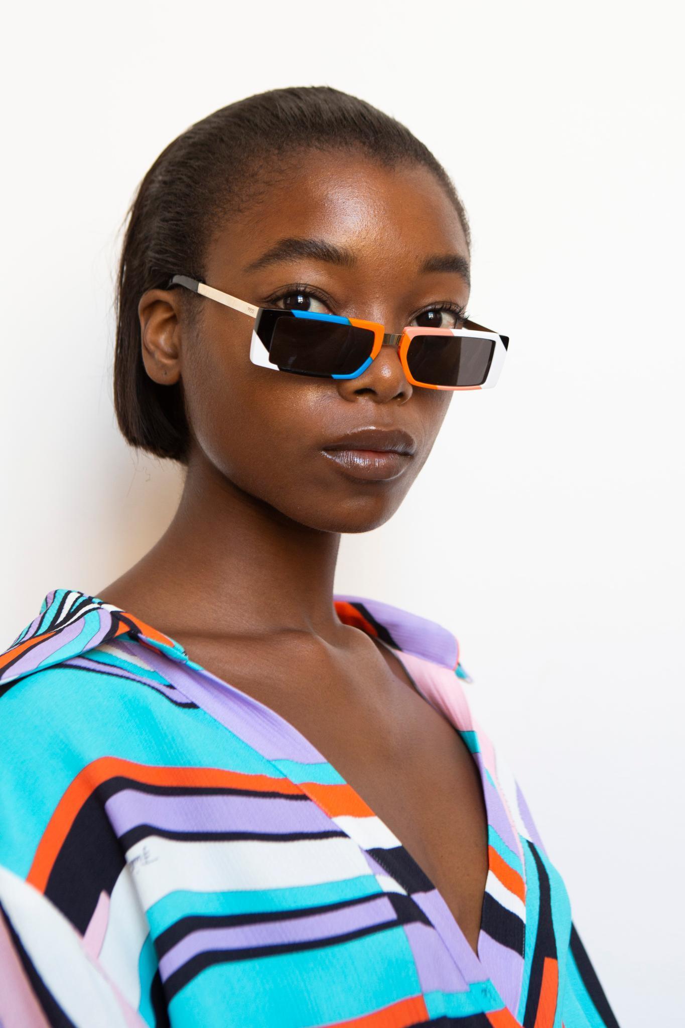 Idées de cheveux noirs courts : modèle noir avec un bob droit peigné en arrière et portant des lunettes.